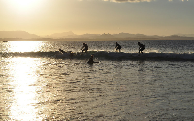Surfers riding waves at Byron Bay