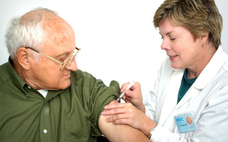 tips for travelling with the elderly, man receiving injection from doctor