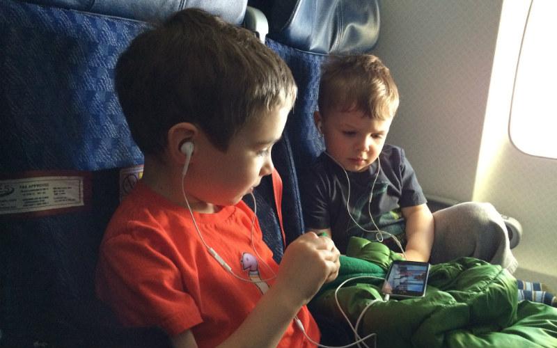 children on plane with headphones
