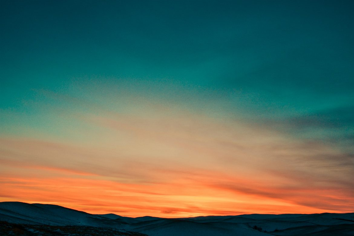 Sunset across snow capped mountains