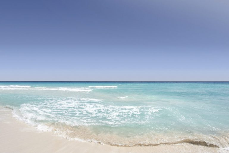 beach with white sand and clear water