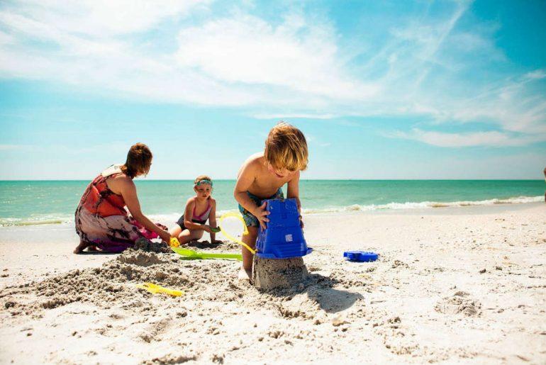 family beach ocean sandcastles