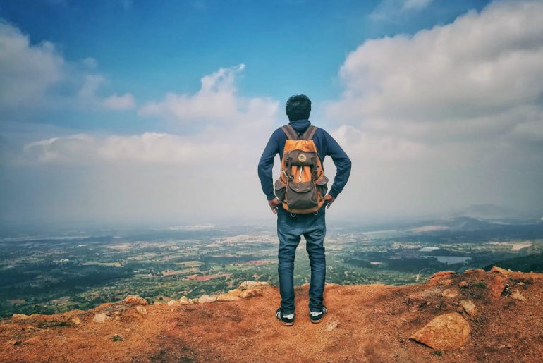 man with backpack on hill